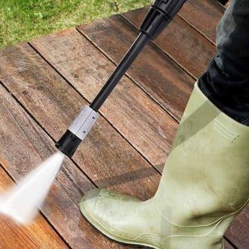 Lanza de una hidrolimpiadora de gasolina limpiando suelo de madedra
