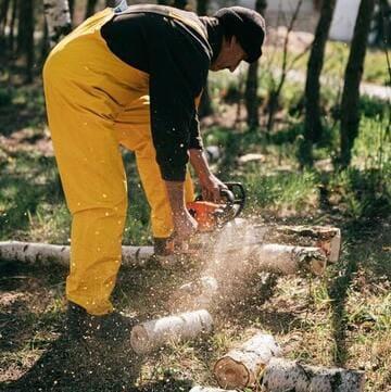 Hombre cortando troncos con una motosierra eléctrica